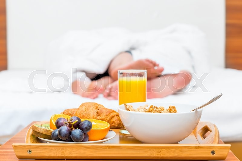 Stock image of 'Couples feet luxuriate in bed and a tray of food'