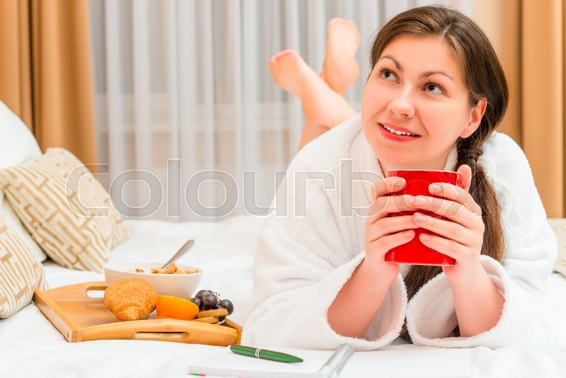 Stock image of 'Thoughtful girl with notepad and breakfast in bed'