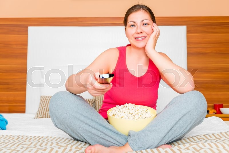 Stock image of 'Girl with a bowl of popcorn watching a fun show on TV'