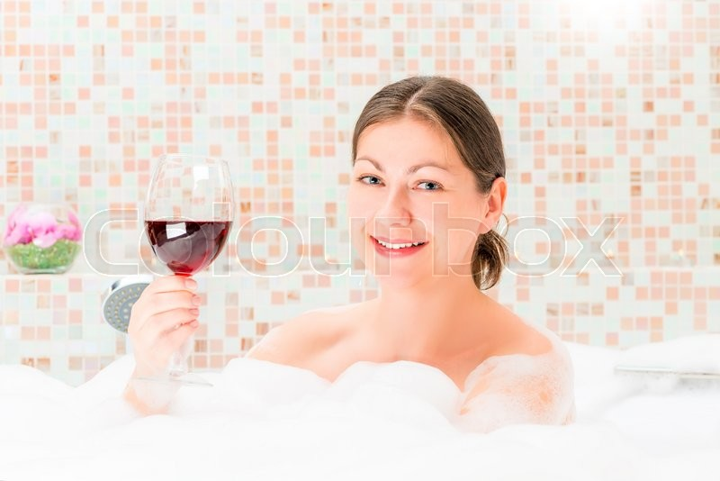 Stock image of 'Portrait of a happy girl in a bath with a glass of drink'
