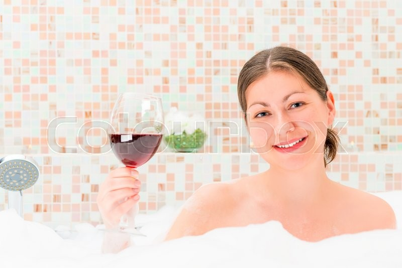 Stock image of 'Girl with a glass of wine in the foam'
