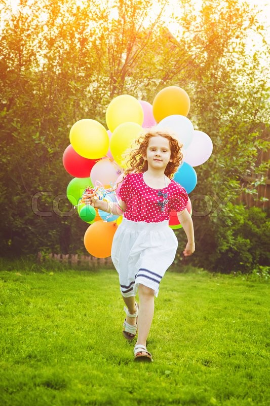 Stock image of 'Little curly girl running with colored balloons. Happy childhood concept. Background toned in instagram filter.'