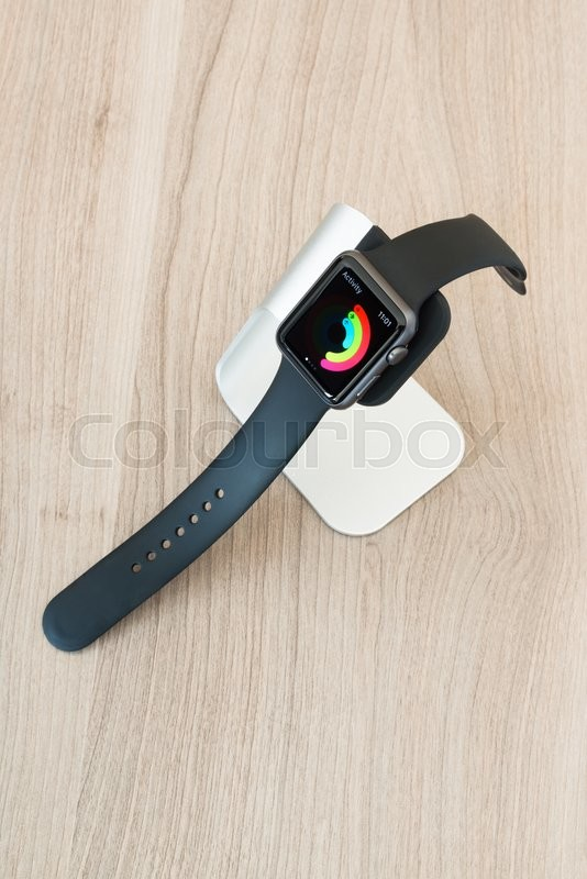 Editorial image of 'Ostfildern, Germany - May 21, 2015: An Apple Watch Sport 42mm with space gray aluminium case and black sport band displaying mediocre daily activity on its screen in a stylish stand by manufacturer Spigen on a wooden table. The Apple Watch is the latest device by computer and smartphone manufacturer Apple Computer and is available since April 2015.'