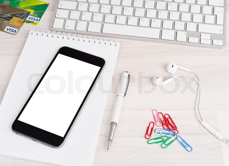 Editorial image of 'Phone with white isolated screen with a notebook and pen'