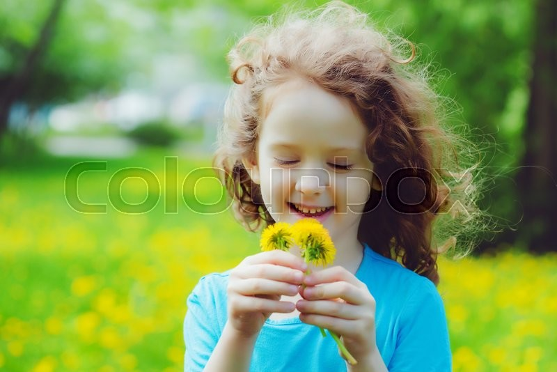 Stock image of 'Little girl with yellow dandelions in the field. Background toning to instagram filter.'
