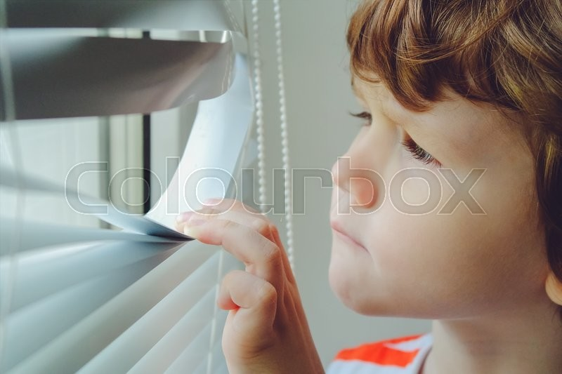 Stock image of 'Little child looking out the window through the blinds. Background toning to instagram filter.'