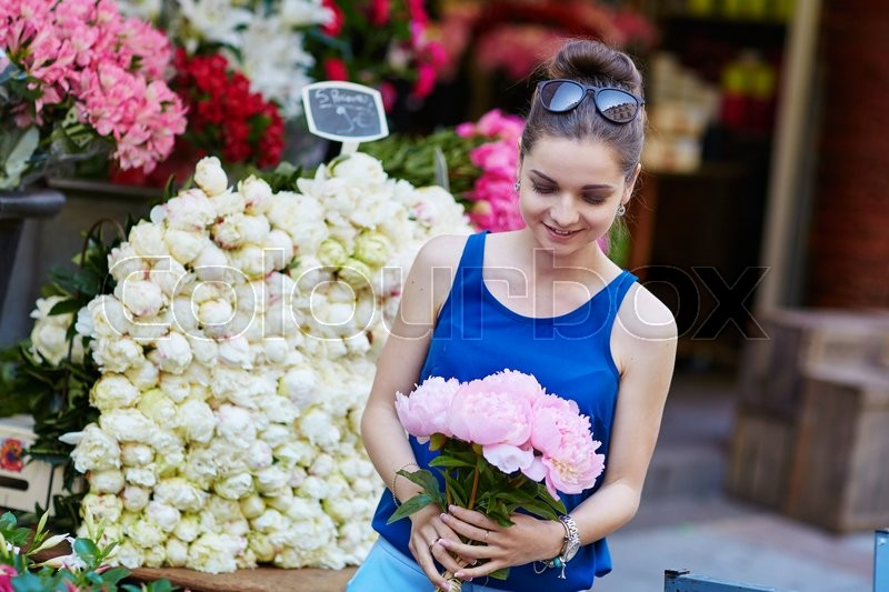 Stock image of 'Beautiful young Parisian woman selecting pink peonies in French flower shop or at market'