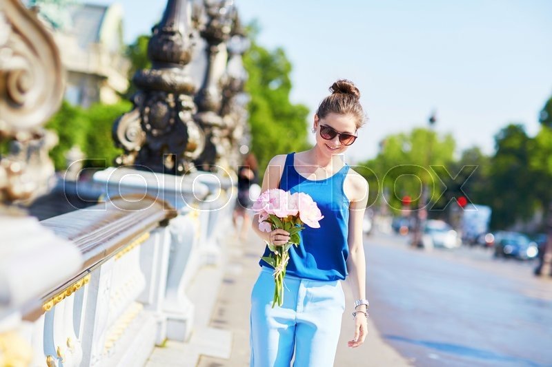 Stock image of 'Beautiful young Parisian woman in blue blouse with bunch of pink peonies on Pont Alexandre III in Paris, France'