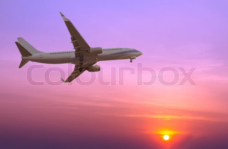 Stock image of 'Commercial airplane flying at sunset'