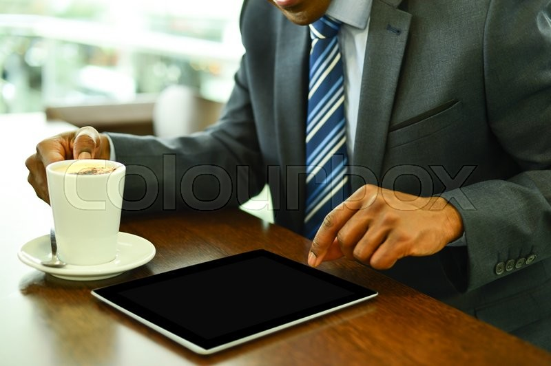 Stock image of 'Businessman operating his digital tablet at cafe'