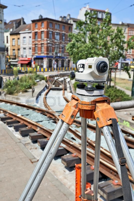 Editorial image of 'BRUSSELS, BELGIUM -16 JULY 2015: Land Surveying on construction site and some workers repair and replace rail trams in Brussels at Verboekhoven square in Schaerbeek.'