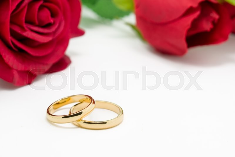 Stock image of 'Wedding rings and artificial rose on white background, horizontally Selective focus\'