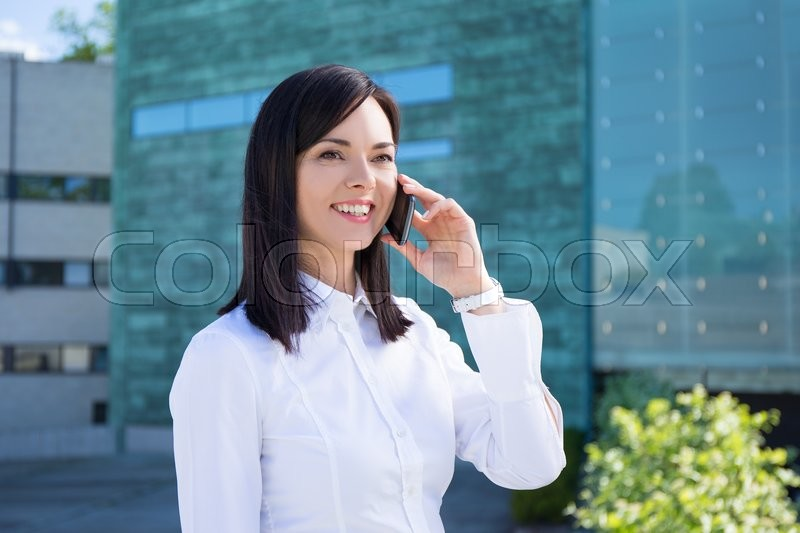 Stock image of 'young beautiful business woman talking on smartphone at street'