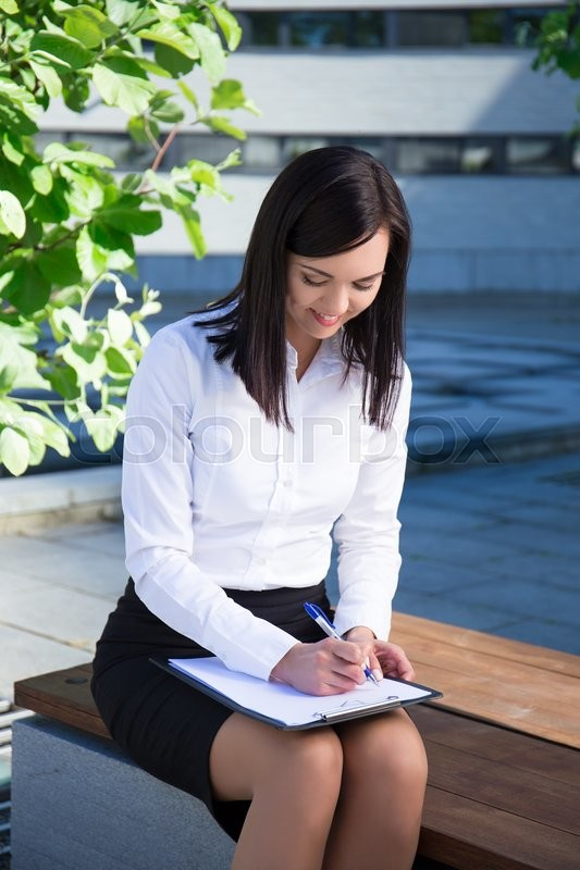 Stock image of 'young beautiful business woman writing something on clipboard in city park'