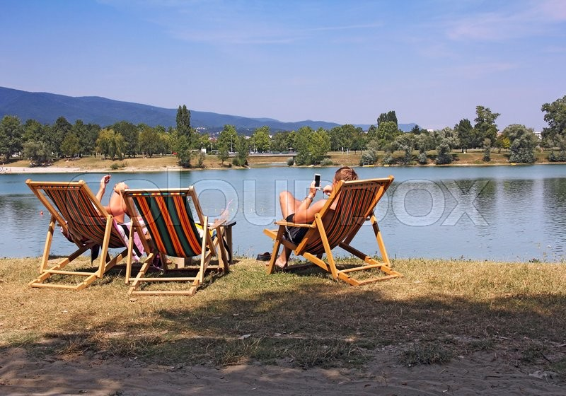 Stock image of 'Two young people in colorful deckchairs on the lake shore\'