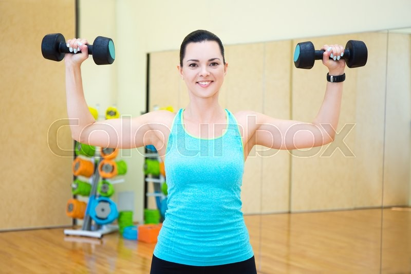 Stock image of 'happy young beautiful woman exercising with dumbbells in gym'