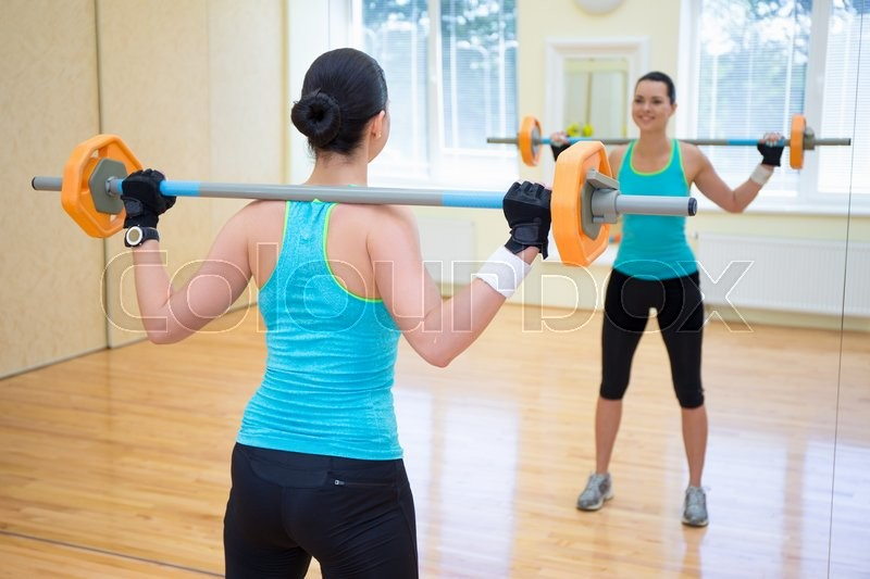 Stock image of 'bodybuilding concept - back view of young woman exercising with barbell in gym'