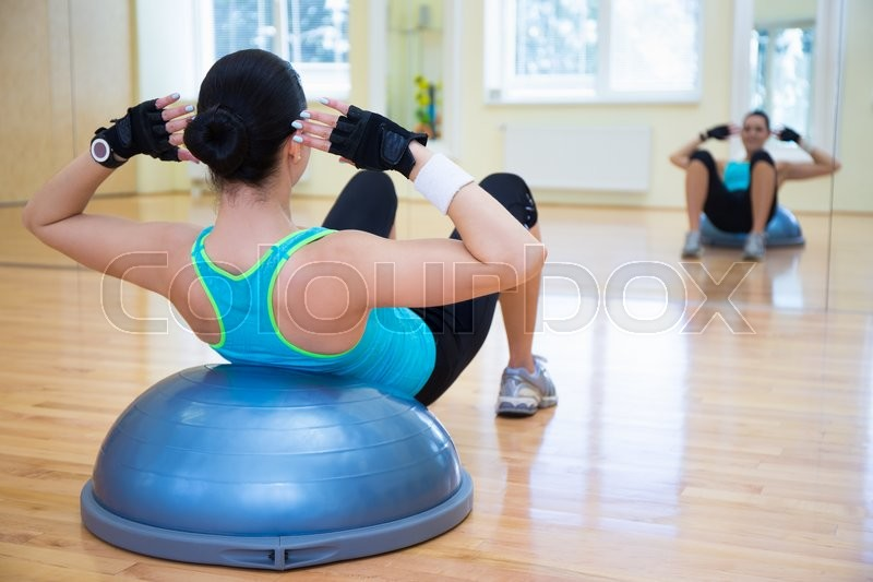 Stock image of 'young woman doing exercises on bosu ball in gym'