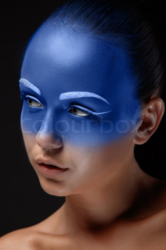 Stock image of 'Portrait of a young woman who is posing covered with blue paint in the studio on a black background. '