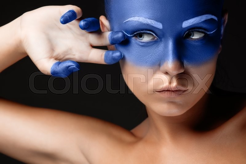Stock image of 'Portrait of a young woman who is posing covered with blue paint in the studio on a black background. girl's hand around the face and painted blue'