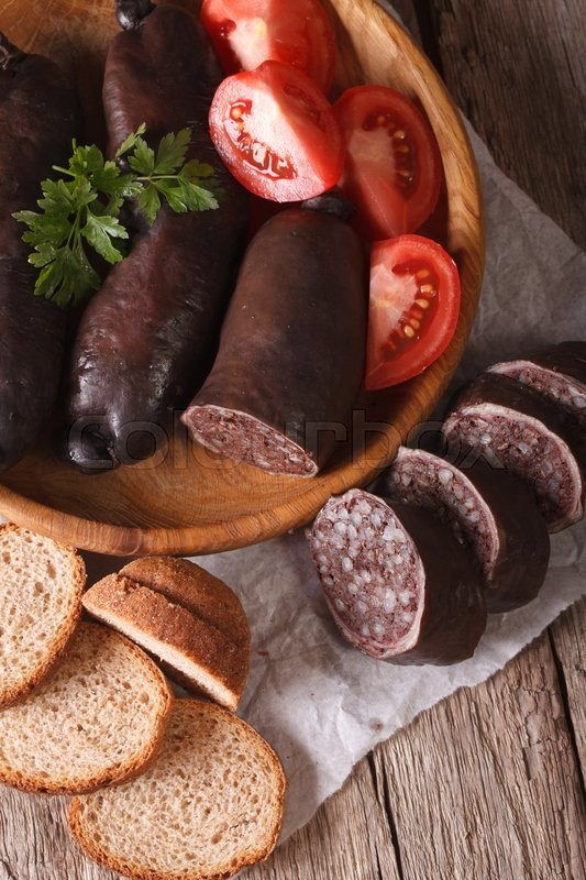 Stock image of 'Fresh black pudding with tomato on a plate close-up. vertical top view\'