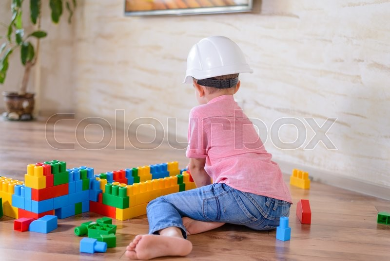 Stock image of 'Young boy wearing hardhat playing indoors sitting on a wooden floor grinning as he holds up a large colorful plastic building block'