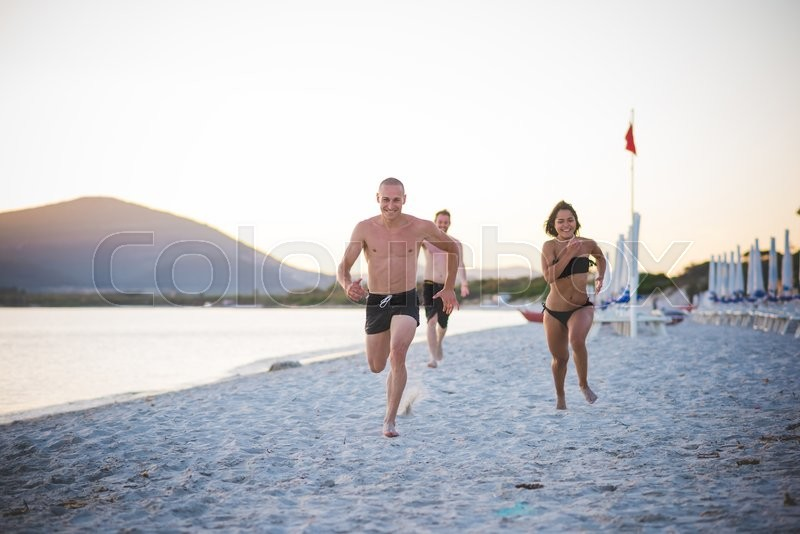 Stock image of 'Group of young multiethnic friends running in swimsuit on the beach at sunset - friendship, freedom concept - Couple of friends challenging themselves on a running race on the beach at sunset'