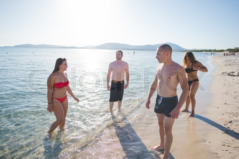 Stock image of 'group of young multiethnic friends women and men at the beach in summertime '