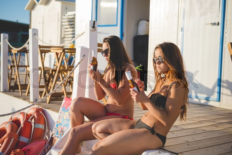 Stock image of 'Two young beautiful friends women at the beach in summertime sitting on the stairs of a bar having a beer.- relax, happy hour, friendship concepts'