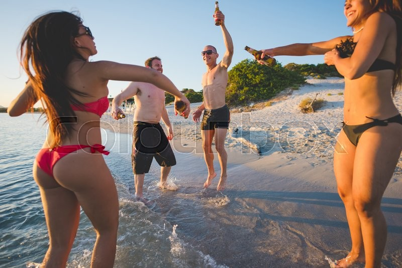 Stock image of 'group of young multiethnic friends women and men at the beach in summertime toasting and drinking beer jumping and dancing - friendship, carefreeness concept'