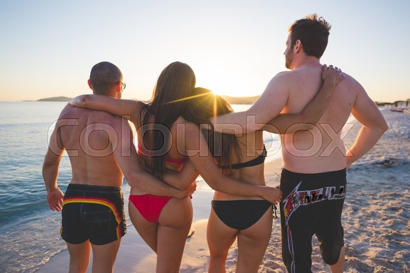 Stock image of 'group of young multiethnic friends women and men at the beach in summertime sunset walking hugging on the foreshore smiling from back - team, friendship, tourism concept - lens flare due to backlighting'