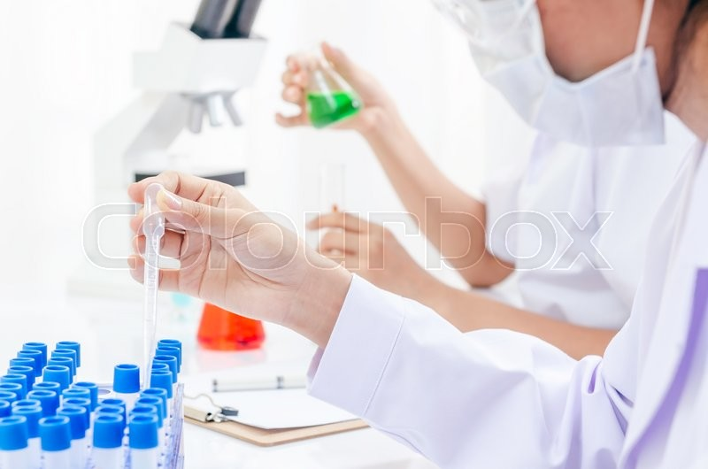 Stock image of 'physicians examining and testing different liquids in tubes'