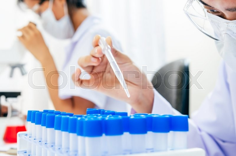 Stock image of 'researcher working on liquid test in tube'