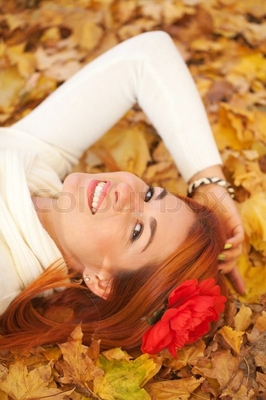 Stock image of 'Red-haired young woman lying among red leaves in autumn forest. Outdoor portrait'
