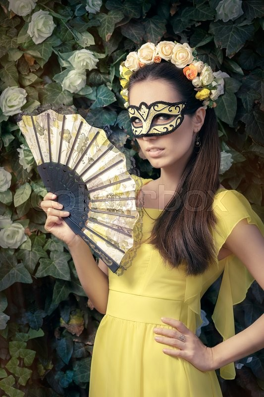 Stock image of 'Portrait of a mysterious masked woman holding a fan'
