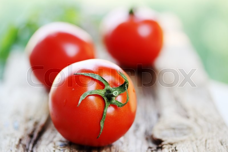 Stock image of 'Fresh organic tomatoes on a wooden board'