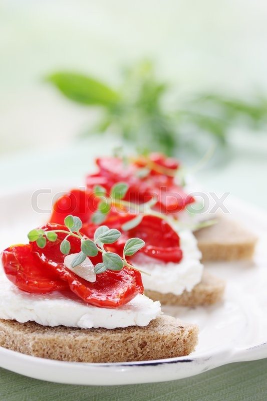 Stock image of 'Canapes of cheese with sun-dried tomatoes and garlic'