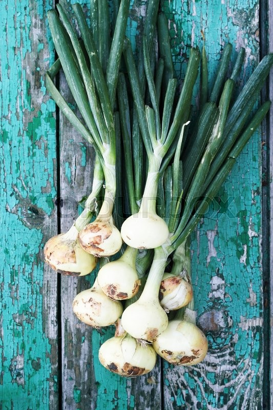 Stock image of 'Fresh organic onions on a wooden board'