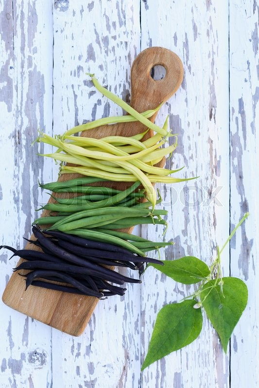 Stock image of 'pods of fresh long beans on a wooden board'