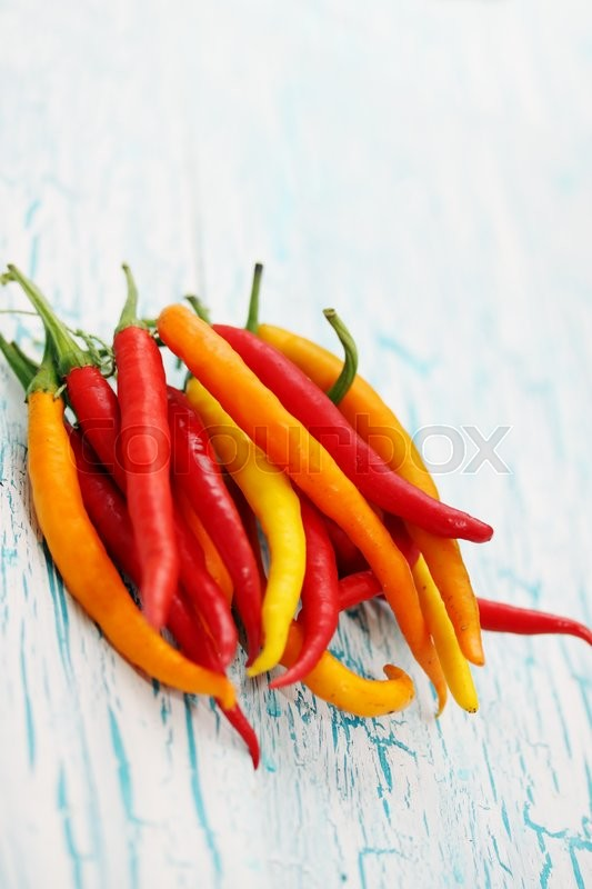 Stock image of 'bunch of small chili peppers on a wooden board'