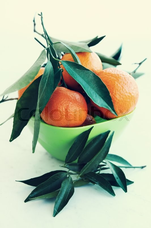 Stock image of 'Fresh juicy tangerines in a green bowl'