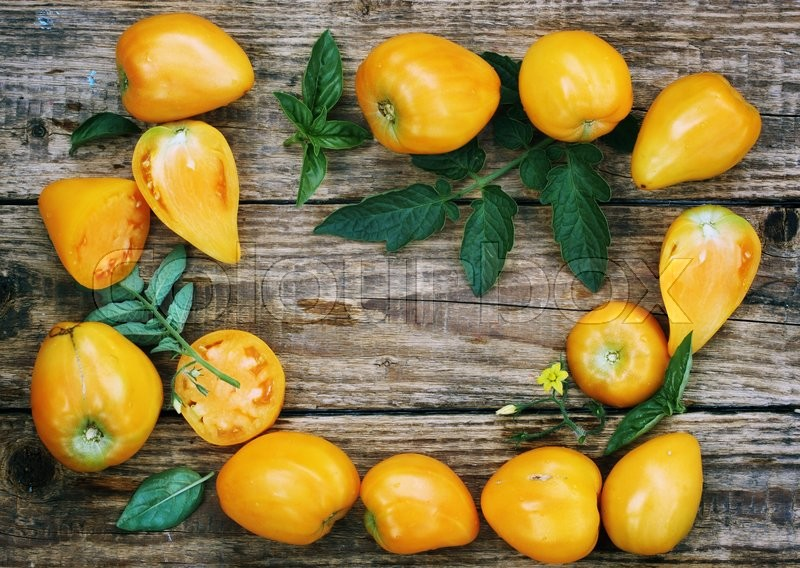 Stock image of 'Fresh juicy yellow tomatoes on a wooden board'