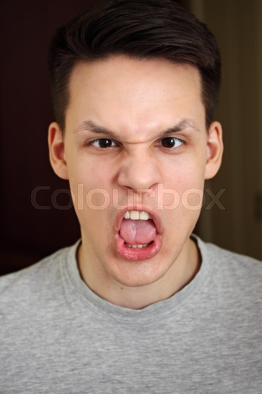 Stock image of ' a young man with a grimace on his face'