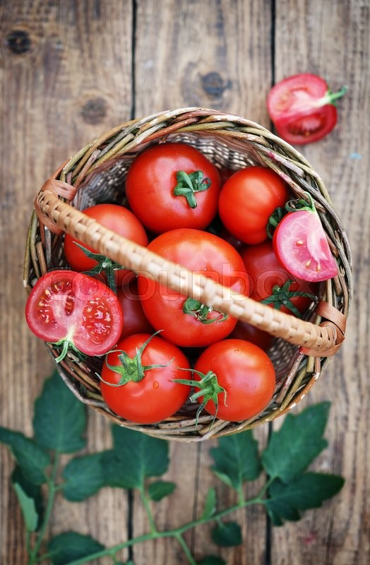 Stock image of 'domestic tomatoes in a basket on a wooden table'