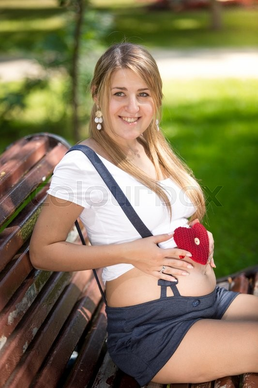 Stock image of 'Portrait of happy pregnant woman posing with red knitted heart'