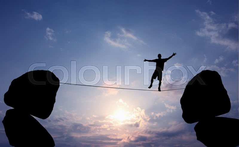 Stock image of 'Highline walker in blue sky between two rocks concept of risk taking and challenge'