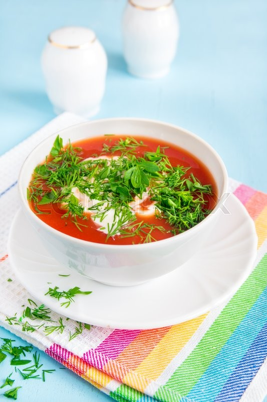 Stock image of 'Homemade tomato cold soup with cream cheese and fresh herbs on blue wooden table'