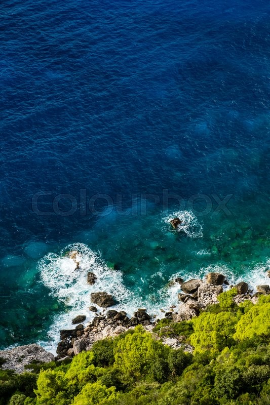 Stock image of 'Aerial view of stony seashore with blue sea and fresh green vegetation'