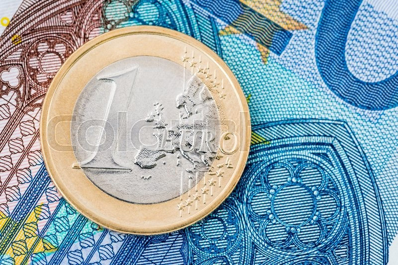 Stock image of 'Detail of one euro coin on blue banknote background'