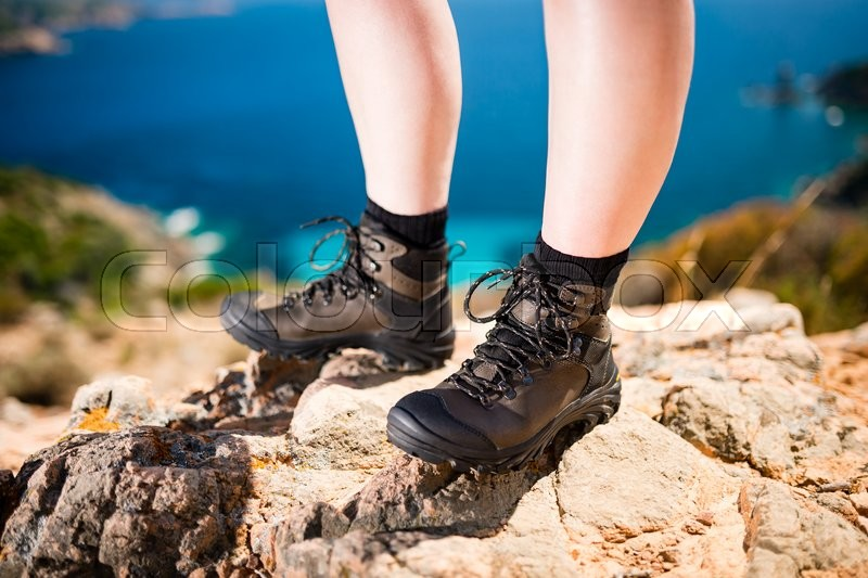 Stock image of 'Detail of women legs in brown leather trekking shoes standing on rock in beautiful nature'